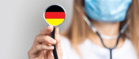 Doctor german care lucreaza in sistemul sanitar german femeie care se află în plan secund cu o mască sanitară pe față și cu stetoscopul în ambele urechi, iar în plan principal este continuarea stetoscopului pe care se afla colorat steagul Germaniei cu negru, roșu și galben.